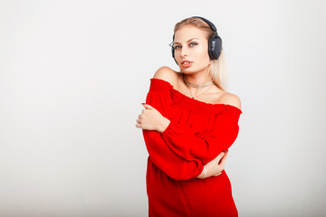 Portrait of a beautiful young DJ girl with headphones in a red dress listening to music on a gray background