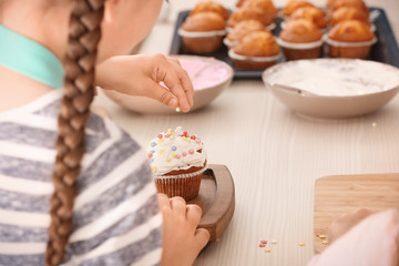 Girl decorating cupcake during cooking classes