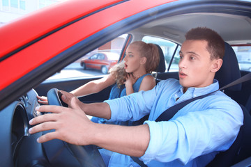 Frightened young couple sitting in car Wall mural