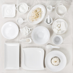 Big set of empty white porcelain plates and other tableware different size and shapes with white breakfast ingredients over white linen tablecloth. Flat lay