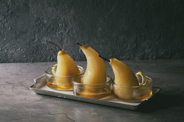 Traditional dessert poached pears in white wine served in glass bowls with syrup and lemon zest over gray texture table.