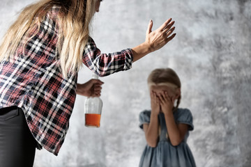 Woman with bottle of alcohol abusing little girl on grey background