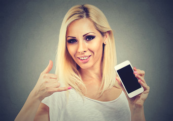 Closeup of a young woman pretty smiling holding phone showing call me sign hand gesture looking at you camera