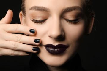 Beautiful woman with stylish make up and long eyelashes on black background