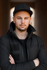 Stylish portrait of a young handsome man in a black baseball cap with a black winter jacket on the street