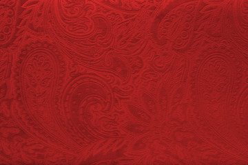 Red velvet fabric with a vintage elegant floral pattern or a luxury texture.