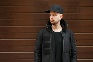 handsome young hipster man in a black stylish baseball cap and winter jacket stands near the wall