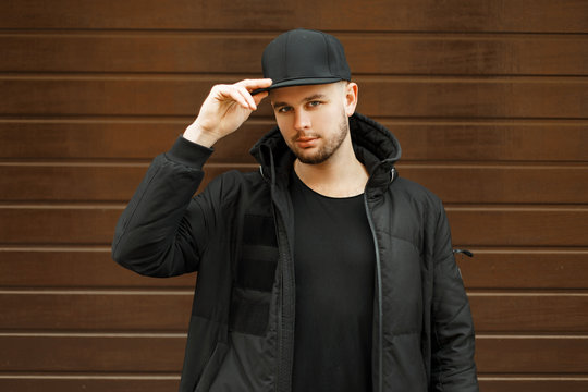 handsome young guy in a black stylish baseball cap and black winter jacket posing near a wooden wall