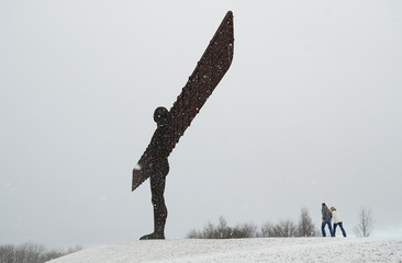 A couple walk in the snow next to the Angel of North near Gateshead