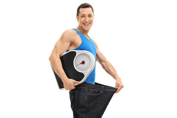 Guy in an oversized pair of jeans holding a weight scale