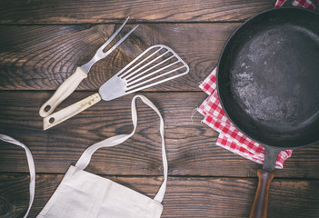 empty black cast-iron frying pan and cooking utensils