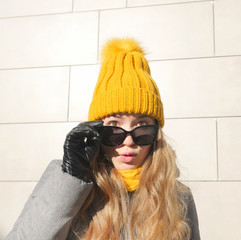 Outdoors lifestyle fashion portrait of stunning blonde girl. Standing outdoors and enjoying life. Wearing stylish gray oversized coat,  yellow scarf, sunglasses and hat. Fashion Girl With Sunglasses.