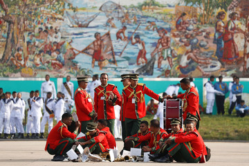 Members of military band and honour guards rest before the welcoming ceremony for Pope Francis at the airport in Dhaka