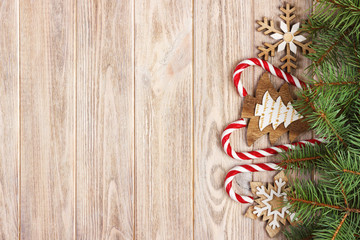 Christmas candy canes and snowflakes on a wooden background