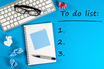 To do list conceptual. Mockup with empty space and workplace with notepad, keyboard at blue background