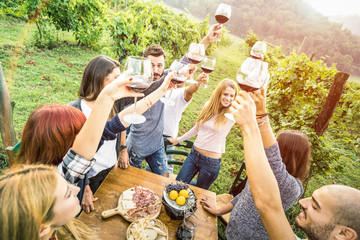 Young friends having fun outdoors drinking red wine glasses - Happy people eating seasonal local food at harvest time in farmhouse vineyard winery - Youth friendship concept on warm vintage filter