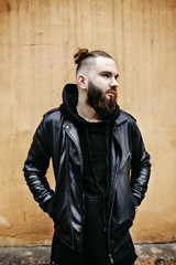Modern young bearded man in black style clothes standing in around urban background.