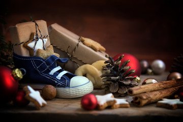 Children's shoe with sweets and gifts for St. Nicholas Day on December 6th at Christmas time on rustic wood, traditional custom in Germany called Nikolaus