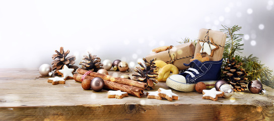 St. Nicholas Day, german Nikolaus, wide panoramic format with kid shoe, sweets and gifts  on rustic wood, background with copy space and blurry lights fades to white
