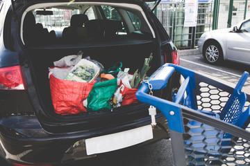 Courses supermarché - Parking voiture client avec sacs de courses dans le coffre