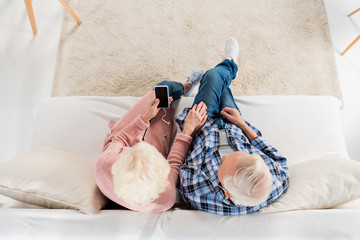 overhead view of senior couple listening music while sitting on sofa at home