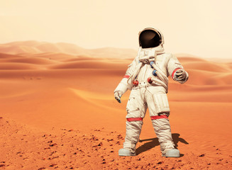 Man in a space suit standing on the red planet Mars. Spaceman conquer a new planet. Concept of the space
