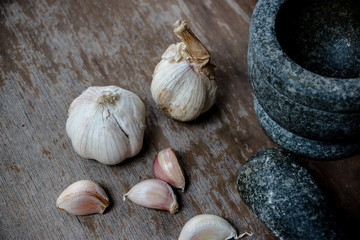 Fresh Garlic bulb, the raw garlic on the wooden background. Around the world, people used garlics in every cuisine. It can used as an effective form of plant-based medicine in many ways.