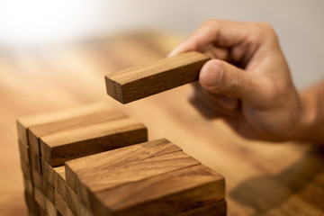 Hand of engineer playing a blocks wood tower game on blueprint or architectural project concept.