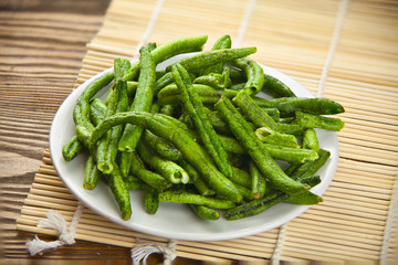 green beans pods on awhite plate on table