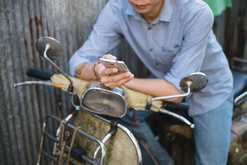 male Asian with smartphone and motorcycle