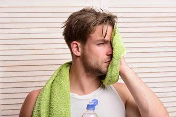 Man with water bottle and green towel