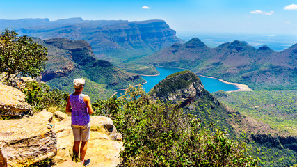 Senior woman enjoying the view of the Blyde River Canyon and Blyde River Dam from the viewpoint at the Three Rondavels along the Panorama Route in Mpumalanga Province of South Africa