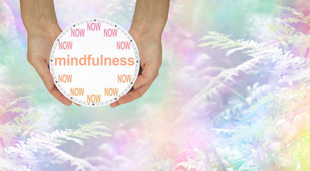 Mindfulness - do it NOW - female hands holding a NOW clock with MINDFULNESS written across the middle against an ethereal rainbow coloured fern background
