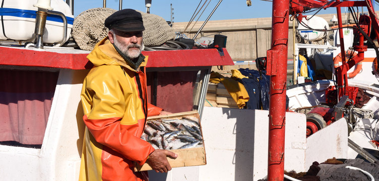 fisherman with a fish box inside a fishing boat