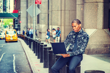 African American businessman in New York. Wearing black flower patterned shirt, tie, young guy siting on street, reading, working on laptop computer. Yellow cab, people on background. .