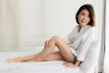 beautiful asian girl white white shirt ralax on white bed next to window curtian with sunlight