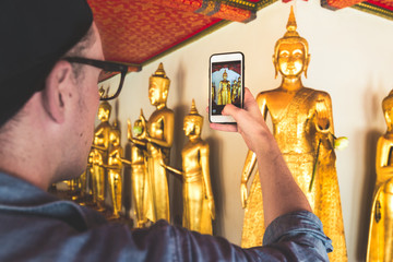 Man holding a smart phone and take picture of a golden buddha in famous temple in Asia. Wat Pho in Bangkok, Thailand