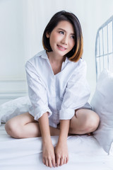 beautiful asian girl white white shirt ralax on white bed next to window curtian with sunlight beauty skin concept