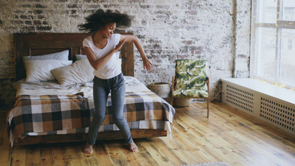 Attractive mixed race young joyful woman have fun dancing near bed at home