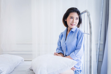 beautiful asian girl casual costume ralax on white bed next to window curtian with sunlight beauty skin concept