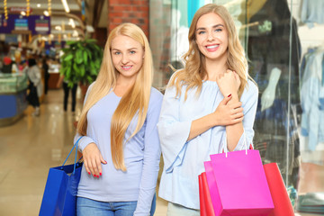 Young beautiful women with shopping bags in modern mall