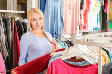 Young beautiful woman choosing clothes in shop