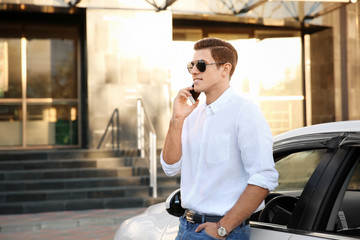 Young man talking on phone near car outdoors