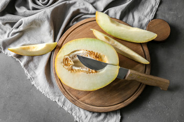 Wooden board with yummy melon and knife on cooking table