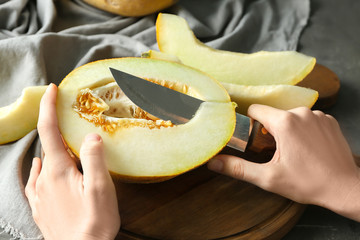 Young woman cutting yummy melon on wooden board