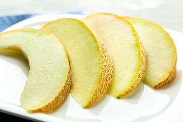 Plate with yummy melon slices on table
