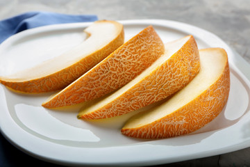 Plate with yummy melon slices on table, closeup