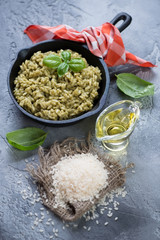 Risotto with spinach in a frying pan and some of its cooking components. Vertical shot over gray concrete background