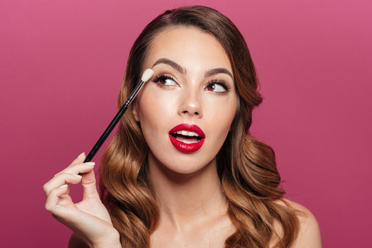 Young pretty lady making make up with brush for eyes isolated