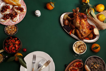 Traditional dinner with roasted chicken, pate and tomato bruschettas on dark green background. Overhead view, copy space. Family dinner concept.